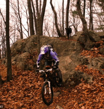 A person mountain biking on a trail in the fall.