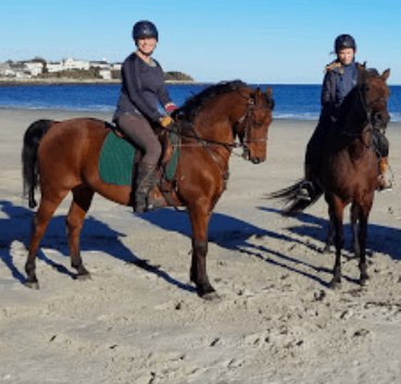 A picture of two female horseback riders on a beach
