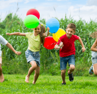 A picture of children playing in the grass with balloons