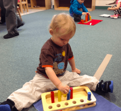 A toddler playing with toys at Keene Montessori School